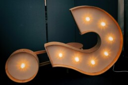 Lit up question mark. Open-ended questions in leadership